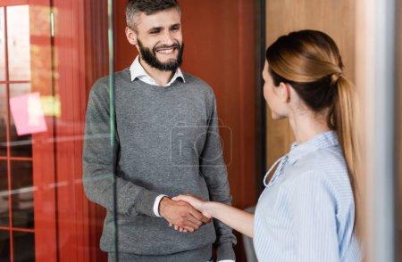 Photo pour Foyer sélectif de l'homme d'affaires heureux et femme d'affaires serrant la main - image libre de droit
