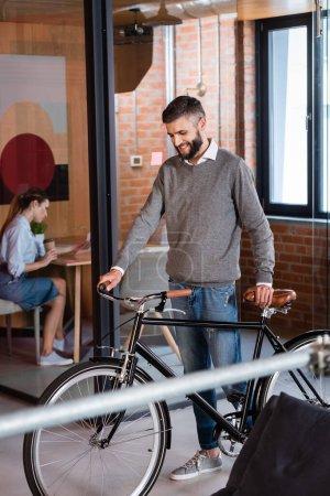 Photo pour Foyer sélectif de l'homme d'affaires heureux debout avec vélo près de femme d'affaires assis dans le bureau - image libre de droit