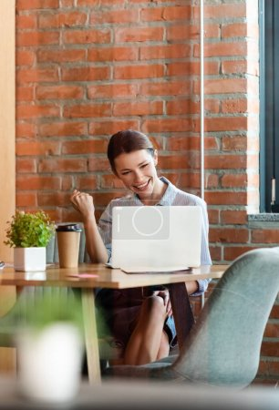 Photo for Selective focus of excited businesswoman using laptop in modern office - Royalty Free Image