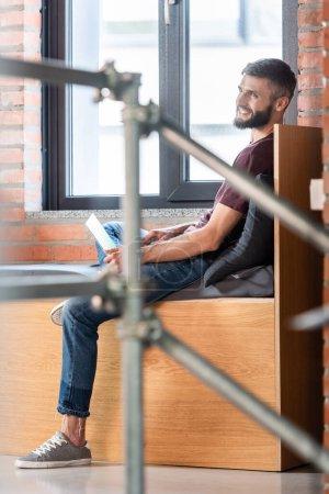 Photo pour Foyer sélectif de l'homme d'affaires heureux assis sur le banc de fenêtre et en utilisant un ordinateur portable - image libre de droit