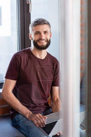 Photo pour Foyer sélectif de l'homme d'affaires joyeux assis sur le banc de fenêtre et tenant ordinateur portable moderne tout en regardant la caméra - image libre de droit