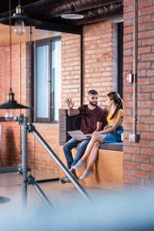 Photo for Selective focus of businesswoman looking at bearded businessman gesturing near laptop while sitting on window bench in office - Royalty Free Image