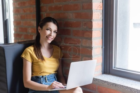 Photo for Smiling businesswoman sitting on window bench and using laptop in office - Royalty Free Image