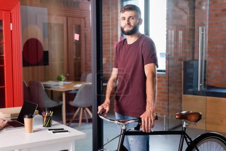 Photo for Bearded businessman standing with bicycle in modern office - Royalty Free Image
