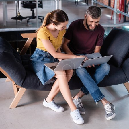 happy businessman and businesswoman using laptops while sitting on sofa