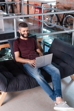 smiling businessman sitting on sofa and using laptop in office
