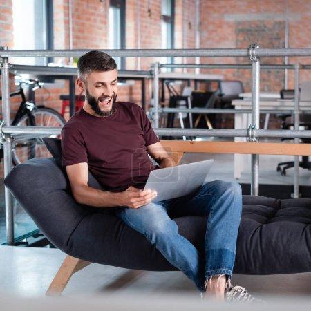 Photo pour Homme d'affaires excité assis sur le canapé et en utilisant un ordinateur portable dans le bureau - image libre de droit