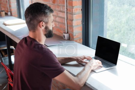 Photo for Selective focus of bearded businessman using laptop with blank screen in modern office - Royalty Free Image