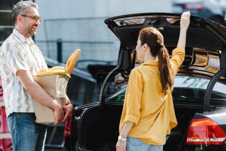 Photo pour Concentration sélective de l'homme souriant tenant sac à provisions avec de la nourriture près de la femme à côté du coffre de la voiture dans la rue urbaine - image libre de droit