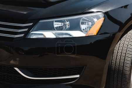 Photo for Headlight of black car with sunlight outdoors - Royalty Free Image
