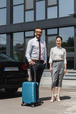 Lächelnder Geschäftsmann mit Koffer in der Nähe von Geschäftsfrau und Auto auf Stadtstraße