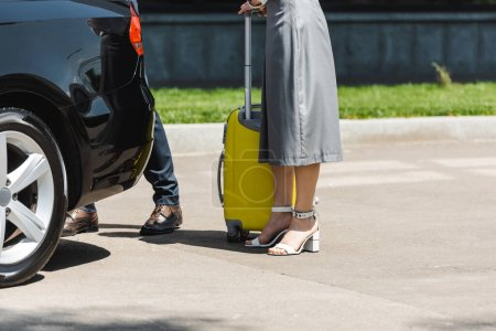 Cropped view of businesswoman with suitcase standing near businessman and car on urban street