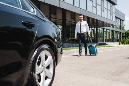 Selective focus of smiling businessman walking with suitcase to car on urban street