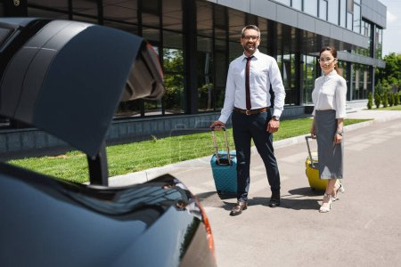 Selective focus of smiling business people walking with suitcases to car with open trunk on urban street