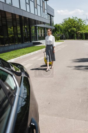 Concentration sélective de femme d'affaires attrayante tenant une valise et marchant jusqu'à la voiture dans la rue urbaine
