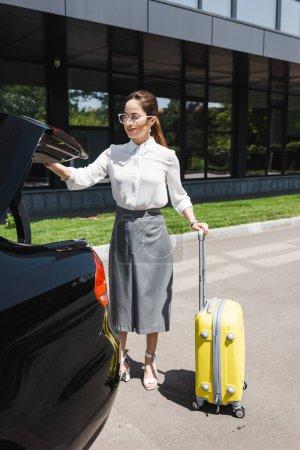 Schöne lächelnde Geschäftsfrau mit Koffer in der Nähe von Auto mit offenem Kofferraum auf der städtischen Straße
