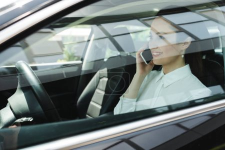 Photo for Selective focus of businesswoman smiling while talking on smartphone on driver seat in car - Royalty Free Image