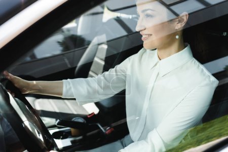 Selective focus of smiling businesswoman driving car