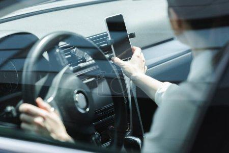 Selektiver Fokus der Geschäftsfrau, die während des Autofahrens ihr Smartphone in der Hand hält