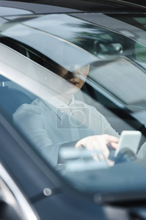Selective focus of businesswoman using smartphone on driver seat in auto