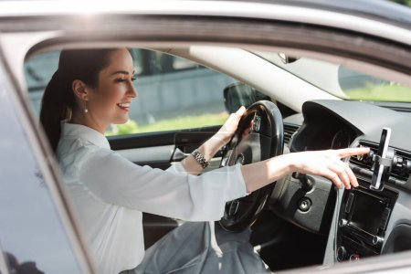 Photo for Side view of smiling businesswoman using smartphone while driving auto - Royalty Free Image