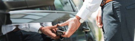 Photo for Panoramic orientation of businessman opening door of car outdoors - Royalty Free Image