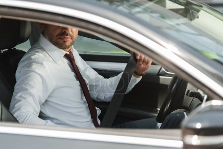 Selective focus of businessman holding seat belt in car