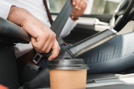 Selective focus of businessman fastening safety belt near paper cup in car