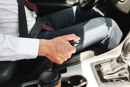 Photo for Cropped view of businessman in formal wear driving car near coffee to go in cup holder - Royalty Free Image