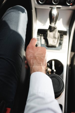 Cropped view of businessman driving car near disposable cup in cup holder