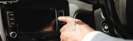 Photo pour Prise de vue panoramique d'un homme d'affaires utilisant un système audio de véhicule en voiture - image libre de droit