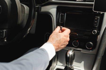 Photo pour Vue recadrée de l'homme d'affaires ajustant le système audio du véhicule tout en conduisant la voiture - image libre de droit