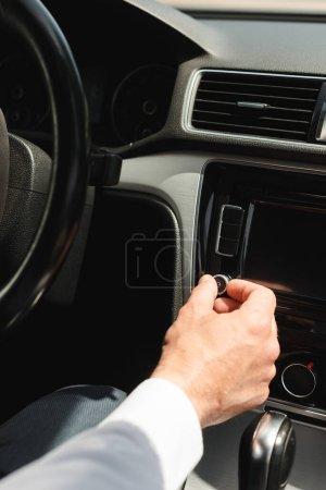 Photo pour Vue recadrée de l'homme d'affaires réglage du volume du système audio du véhicule en auto - image libre de droit