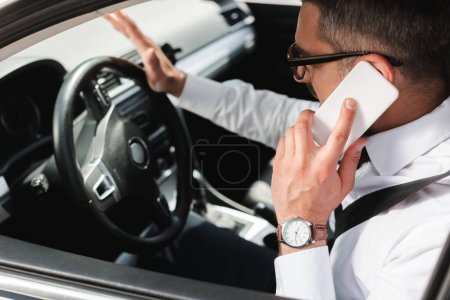 Photo for Selective focus of businessman talking on smartphone while driving car - Royalty Free Image