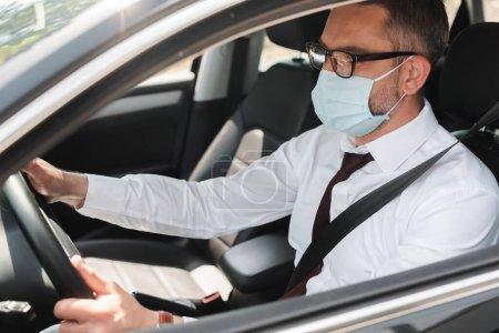 Selektiver Fokus des Geschäftsmannes in medizinischer Maske am Steuer eines Autos