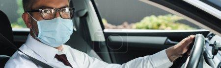Panoramic shot of businessman in medical mask looking at camera while driving car
