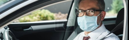 Panoramic orientation of businessman in medical mask looking at camera on driver seat in car