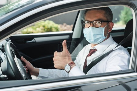 Photo for Selective focus of businessman in medical mask showing thumb up while driving auto - Royalty Free Image