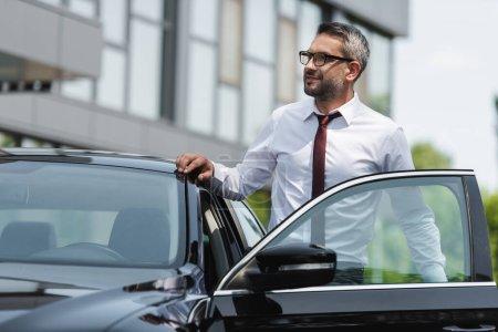 Selektiver Fokus eines gutaussehenden Geschäftsmannes, der in der Nähe eines Autos mit offener Tür auf einer städtischen Straße steht