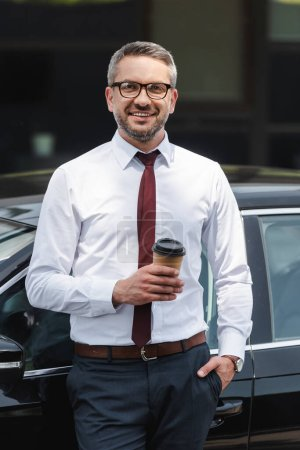 Photo for Handsome businessman holding coffee to go near car and smiling at camera on urban street - Royalty Free Image