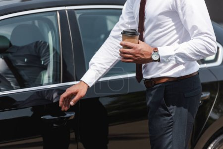 Photo for Cropped view of businessman holding coffee to go and opening car door on urban street - Royalty Free Image
