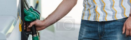 Photo for Panoramic shot of man holding fueling nozzle on gas station outdoors - Royalty Free Image