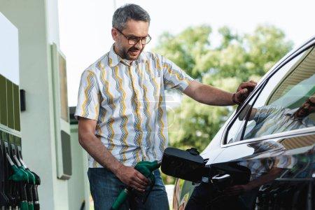 Przystojniak tankuje samochód na stacji benzynowej na ulicy miejskiej.