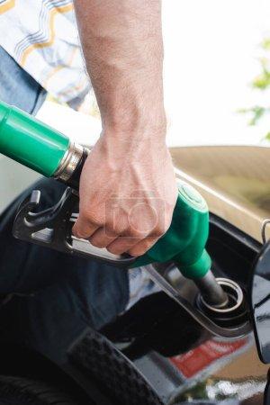 Photo pour Vue recadrée de l'homme tenant la buse de ravitaillement près du couvercle ouvert du réservoir de gaz à l'extérieur - image libre de droit