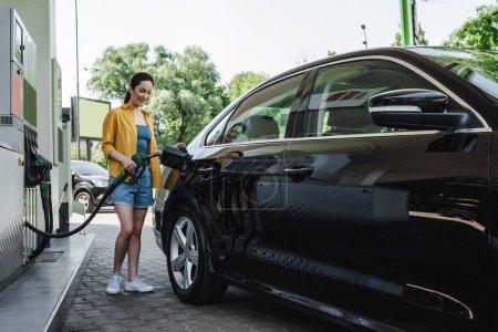 Piękna uśmiechnięta kobieta tankuje samochód na stacji benzynowej