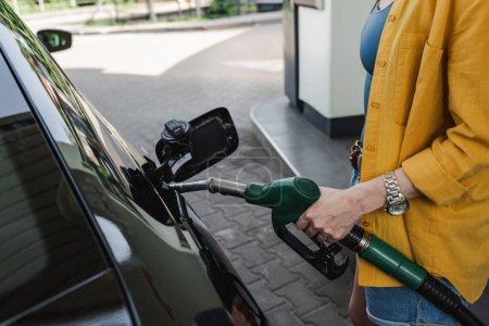 Photo pour Vue recadrée de la femme tenant la buse de ravitaillement près du réservoir d'essence de la voiture sur la rue urbaine - image libre de droit