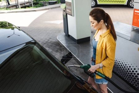 Photo for High angle view of positive woman refueling car on gas station - Royalty Free Image