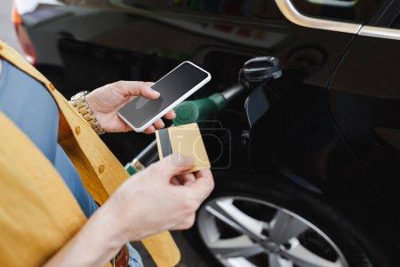 Widok kobiety trzymającej smartfona i kartę kredytową podczas tankowania samochodu na stacji benzynowej