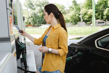Kobieta ze smartfonem i kartą kredytową w pobliżu auto na stacji benzynowej