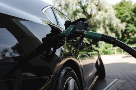 Photo pour Buse de ravitaillement en carburant dans le réservoir d'essence de la voiture sur la station-service sur la rue urbaine - image libre de droit